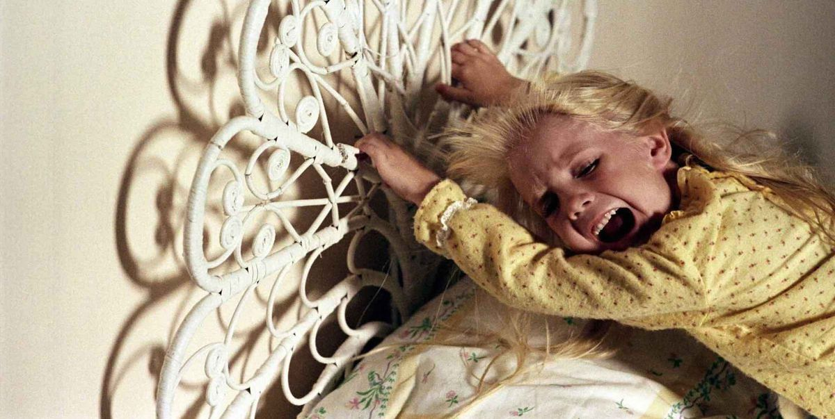 A little girl clings to her bedframe, screaming, as something offscreen tries to pull her away.