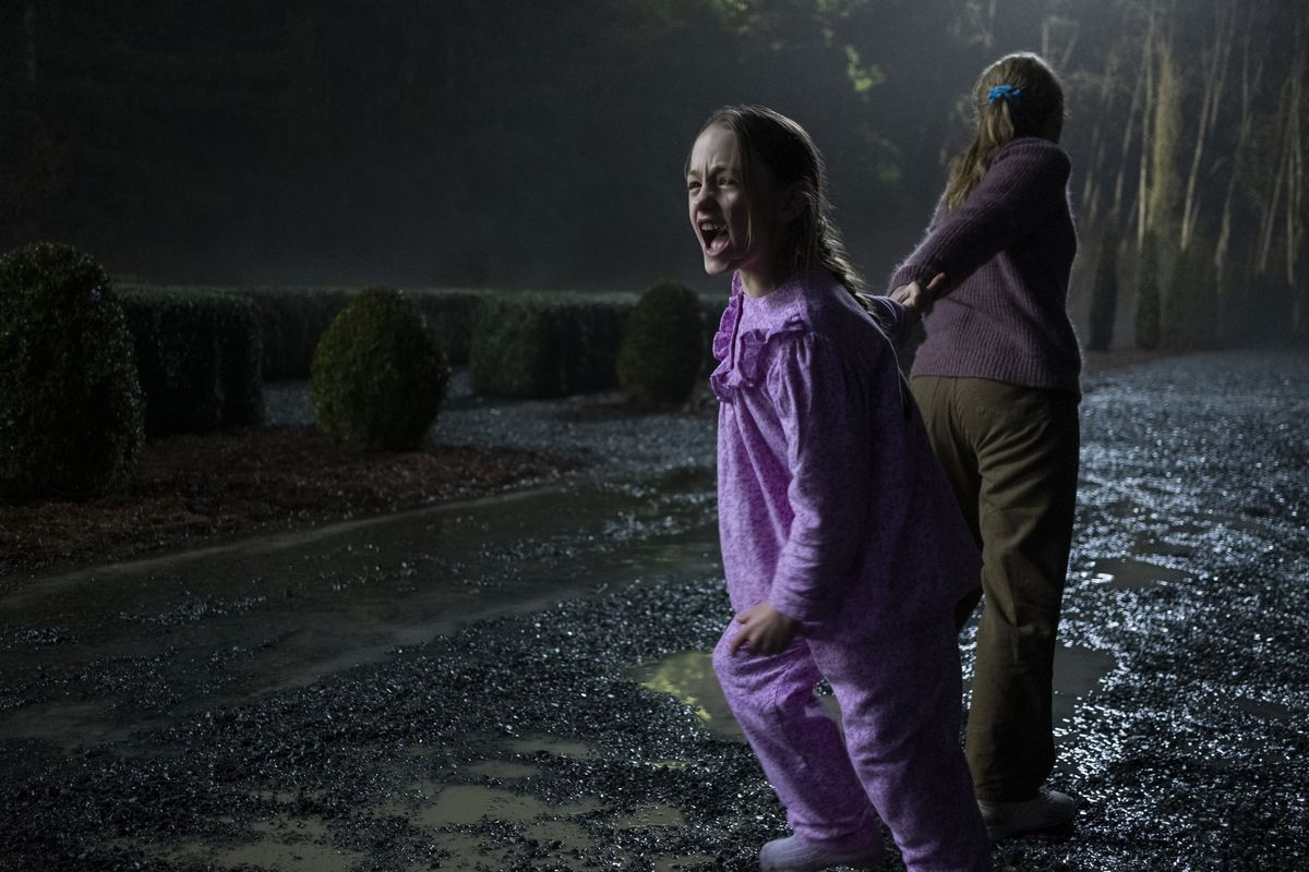 One girl pulls another screaming girl through a big manor garden in The Haunting of Bly Manor