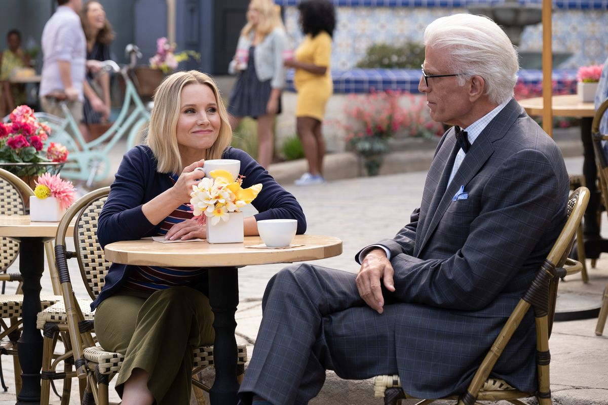 Kristen Bell as Eleanor in The Good place sits at an outdoor cafe, sipping from a white mug while beaming at Ted Danson as Michael the demon, a white-haired older man in a grey suit and black bow tie.