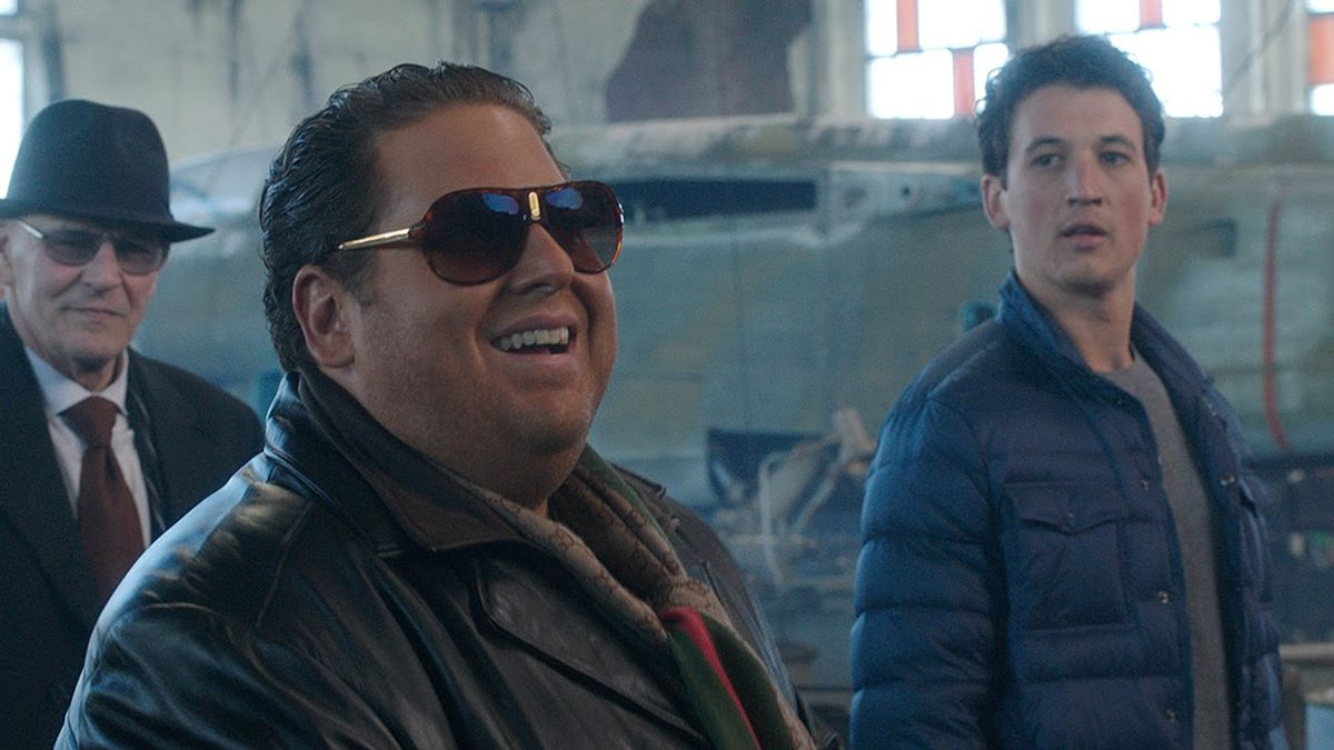 Jonah Hill laughing with big sunglasses on while Miles Teller looks at him awkwardly