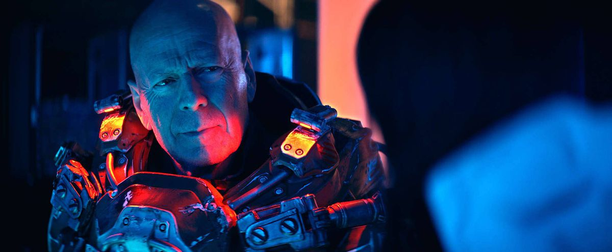 Bruce Willis in a light up armor suit looking tired