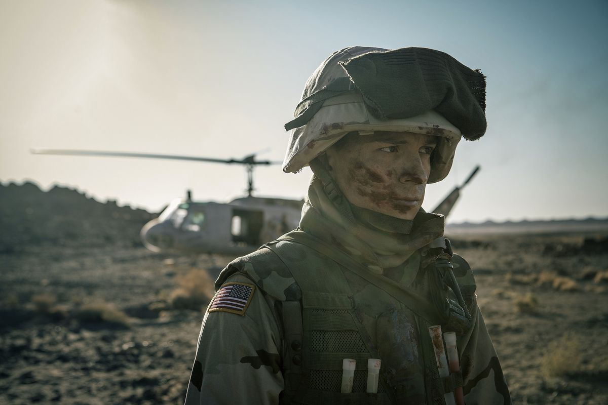Muddy Tom Holland in Army gear in Iraq standing in front of a helicopter
