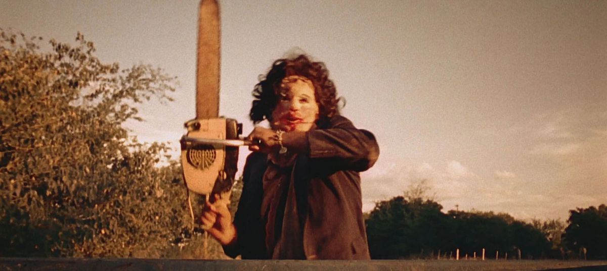 Leatherface chasing after a truck while wielding a chainsaw.