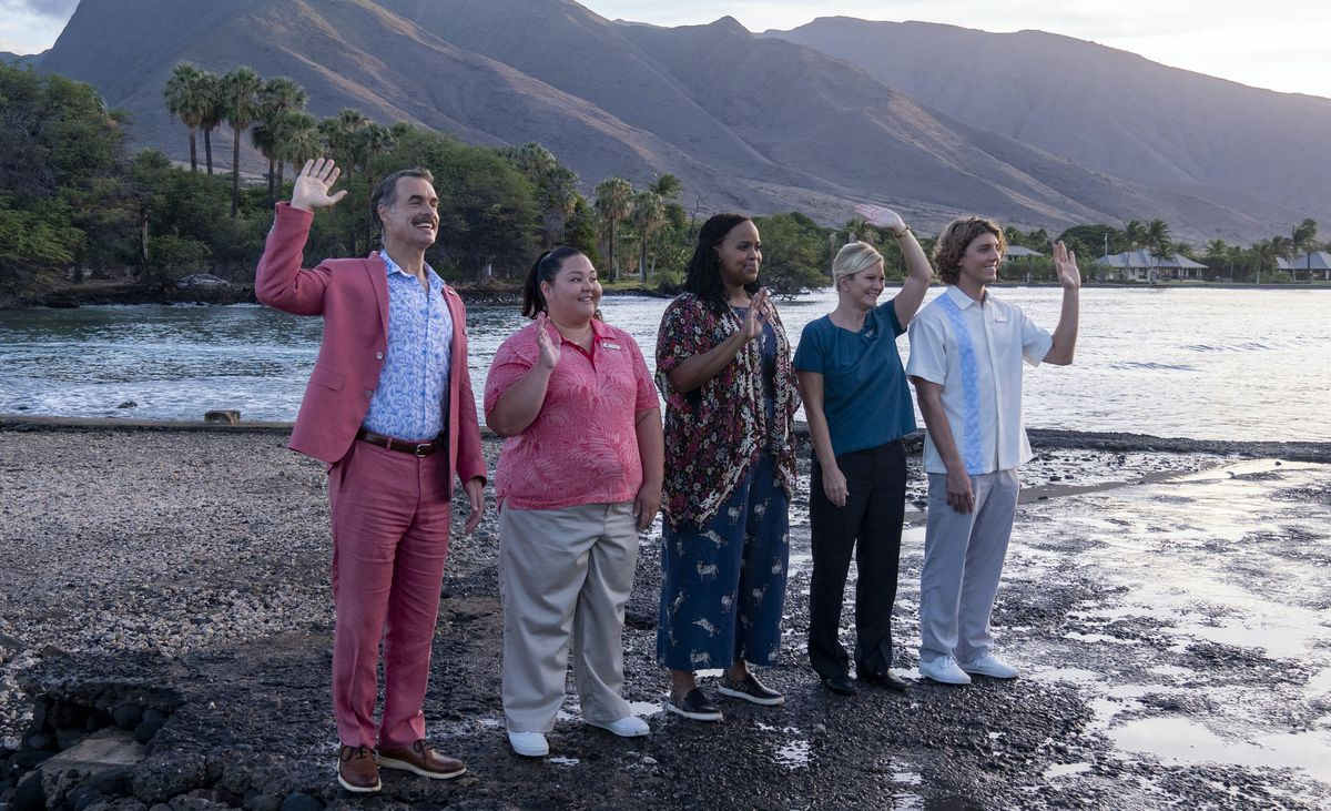 The staff of the White Lotus stands on the beach, offering a friendly wave to the arriving spoiled rich people