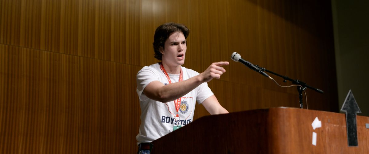 A teenage boy stands at a lectern pointing as he delivers a speech in Boys State