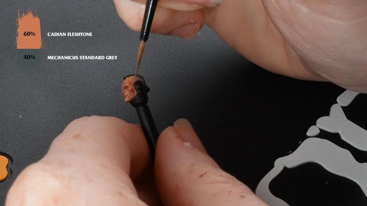 A pair of hands painting the stubble on the head of a Space Marine