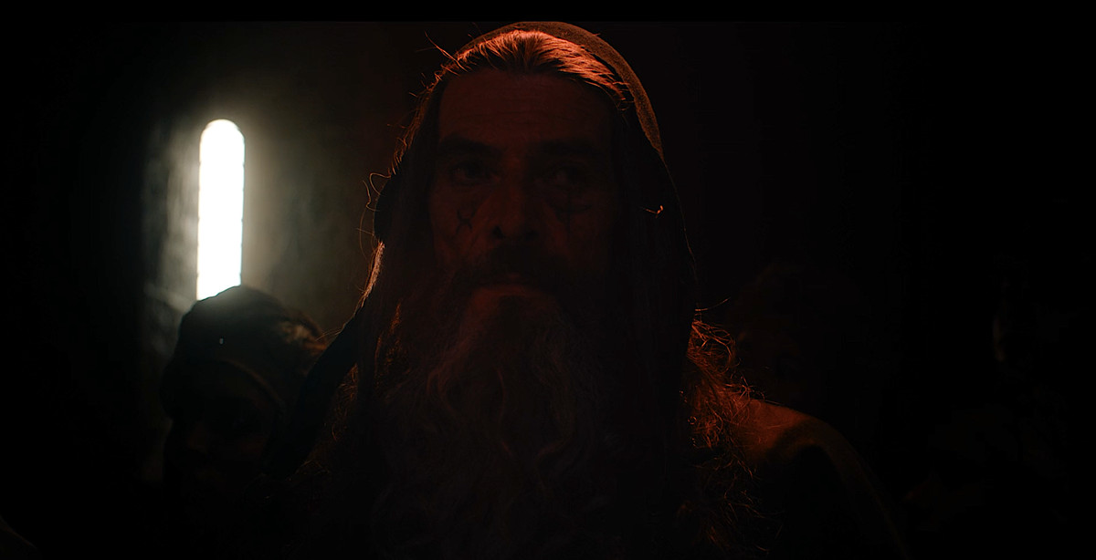 Merlin, in dim, rich red light, casts a spell in David Lowery's The Green Knight