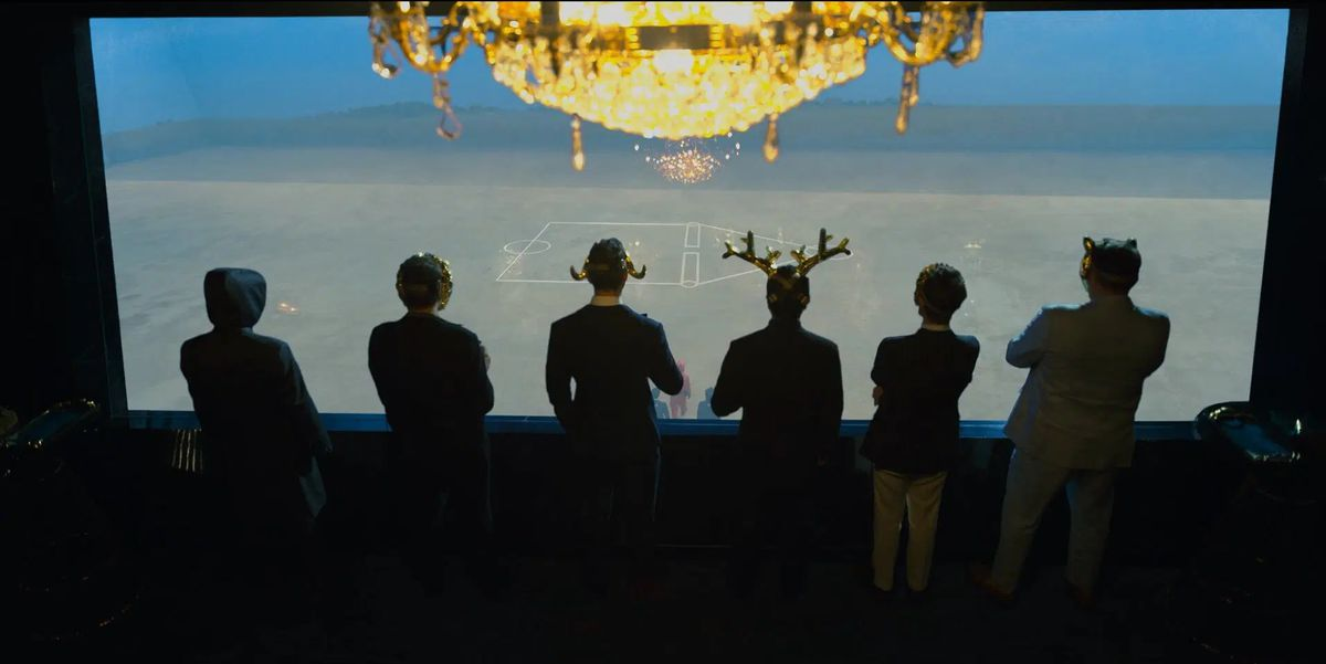 A group of six masked men look down at the field of the final game in Squid Game.